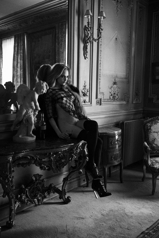 Fotos de Cara Delevingne nua sentada na mesa.