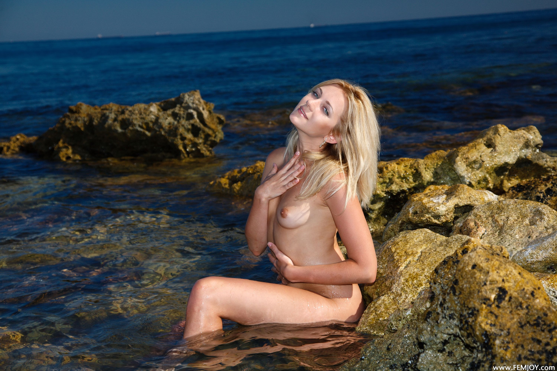Rubia abriéndose junto al mar