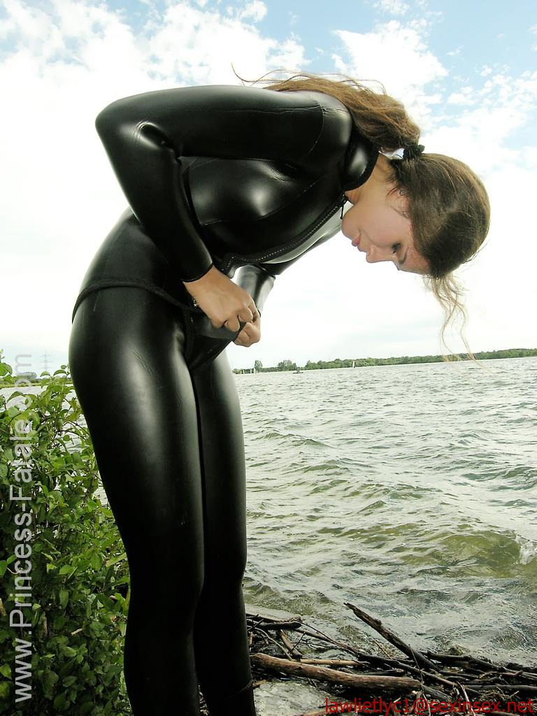 Fetish latex couple of woman in red catsuit and man in black overall with gasmask stock image